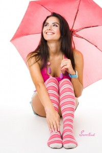 Happy young woman in pink sitting with umbrella